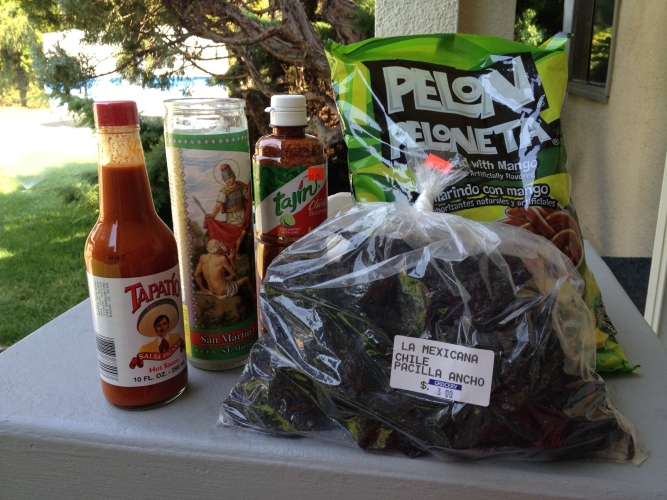Various Mexican goodies: Tapatio sauce, Tajin, St. Martin candle, exotic lollies, and dried ancho chilies.